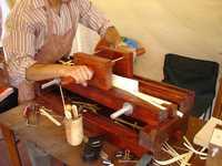 Utilizando un ingenio, los amanuenses cortan los cantos de los libros hasta dejarlos parejos, después de coserlos a mano