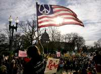 Un manifestante agita en Washington una bandera estadunidense con el símbolo de la paz.