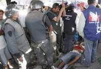 Una persona yace herida entre policías antimotines, después del enfrentamiento de ayer en el poblado minero de Moquegua