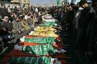 Palestinos oran junto a los cuerpos de las víctimas del ataque israelí a una escuela bajo administración de la ONU en Jabaliya