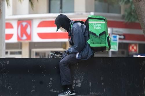 En Paseo de la Reforma, un repartidor de comida rápida revisa sus pedidos e itinerarios en tiempos de contingencia sanitaria.