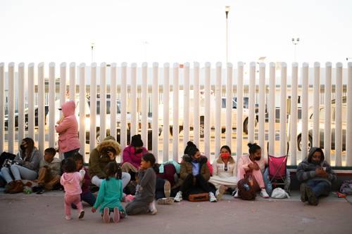 Niños esperan con sus familias en los alrededores de la garita de El Chaparral, en Tijuana, el momento de pasar hacia EU.