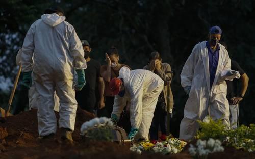 Enfundados en trajes protectores, empleados de un cementerio en Sao Paulo entierran un cadáver ante los lamentos de familiares. Brasil, uno de los países más afectados por la emergencia de salud, alcanzó un total de 370 mil fallecidos, con promedio diario de alrededor de 3 mil decesos.