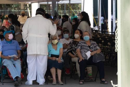 Personas mayores escuchan las instrucciones de un médico en el área de observación tras recibir la vacuna contra el virus del Covid-19 en el Campo Marte.