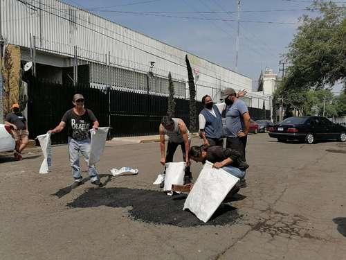Con recursos propios y de manera rústica, vecinos de la calle Vainilla, en la colonia Granjas México, en Iztacalco, repararon algunos de los más de 400 baches que tiene ésta.