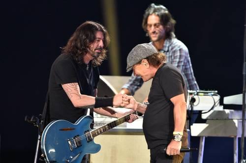 Brian Johnson, de AC/DC (derecha), choca el puño con Dave Grohl, de Foo Fighters, después de actuar con ellos. Foto Afp