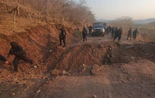 Elementos de la policía de Michoacán vigilan el tramo carretero ubicado entre las localidades de Aguililla y El Aguaje, luego de que presuntos miembros del cártel Jalisco Nueva Generación cortaron la vía.