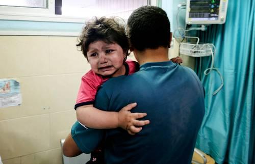 Un palestino sostiene a una niña herida que espera atención médica en el Hospital Al-Shifa, tras un ataque aéreo israelí en la ciudad de Gaza, ayer.