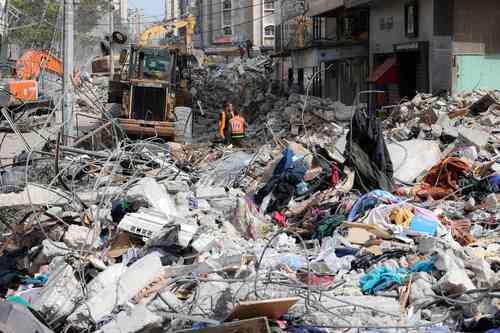 Una excavadora limpia escombros en el distrito residencial Rimal de la ciudad de Gaza ayer, luego del bombardeo masivo israelí en el enclave controlado por Hamas. Los ataques israelíes mataron a 40 palestinos en la franja de Gaza, la peor cifra diaria de muertos en casi una semana.