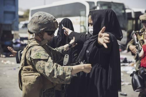 Una marine de Estados Unidos revisa a una mujer afgana en el centro de control de evacuación del aeropuerto internacional Hamid Karzai en Kabul, Afganistán.