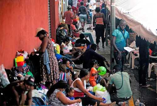 Personas originarias de Haití esperan afuera de un albergue en Monterrey, Nuevo León, la resolución a su solicitud de regular su estancia en México.