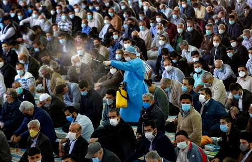 Un empleado municipal rocía desinfectante sobre los asistentes a una mezquita de Teherán, capital de Irán.